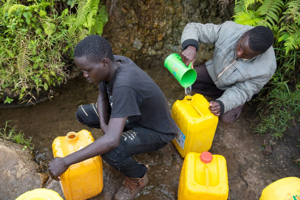 Men pour water from stream into jerry cans