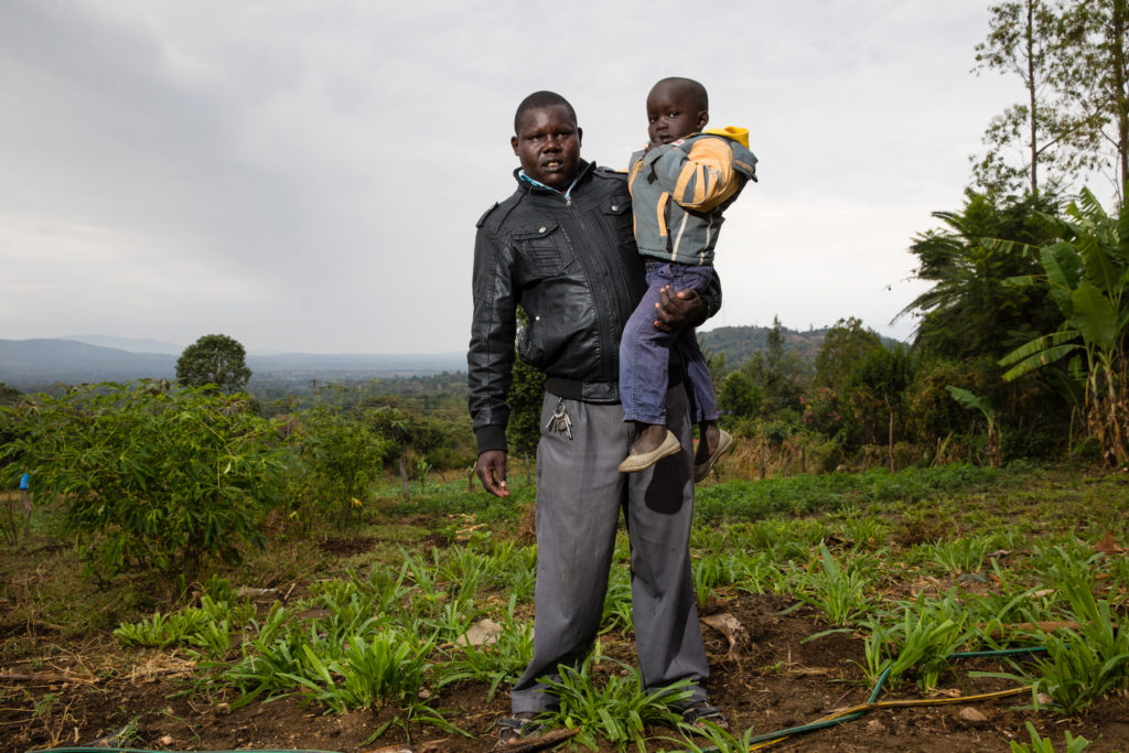 Man stands and holds child