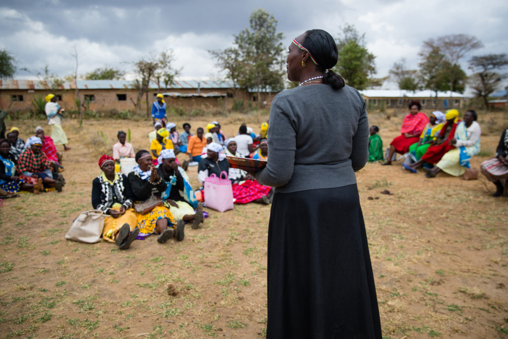 Woman stands and talks to group of women sitting on the ground
