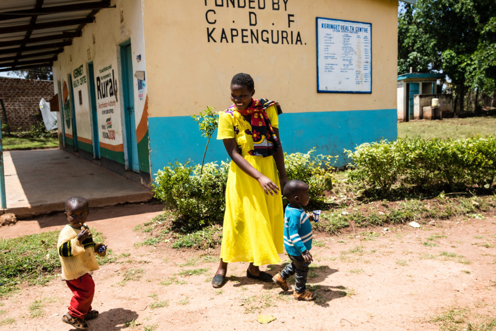 Woman walks with two children