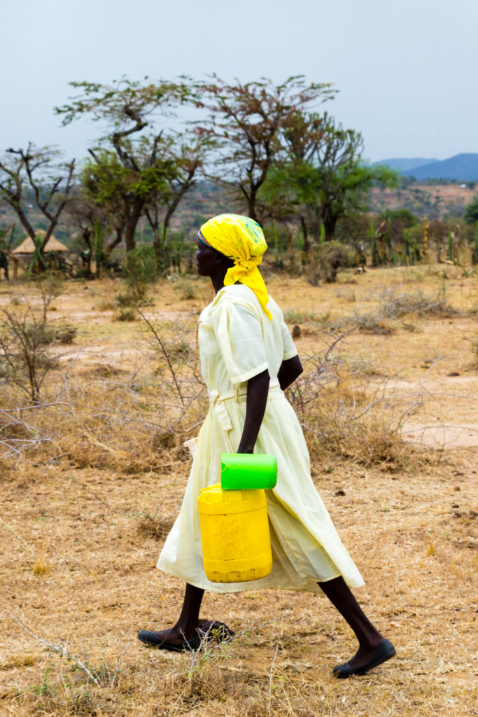 Woman carries jerry can