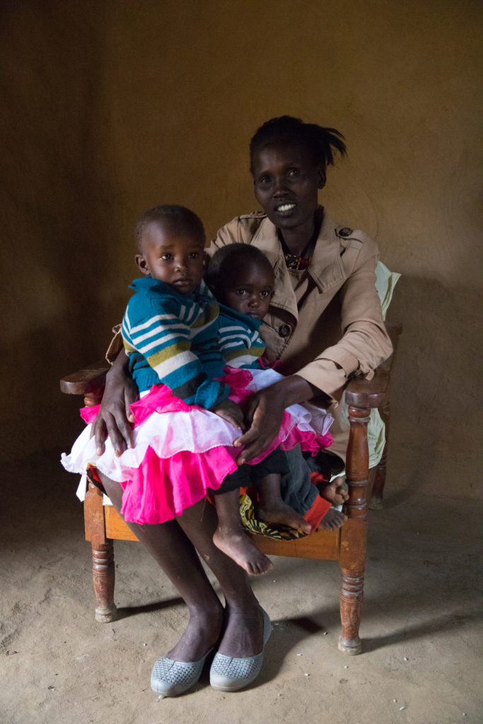 Woman sits with two children in her lap