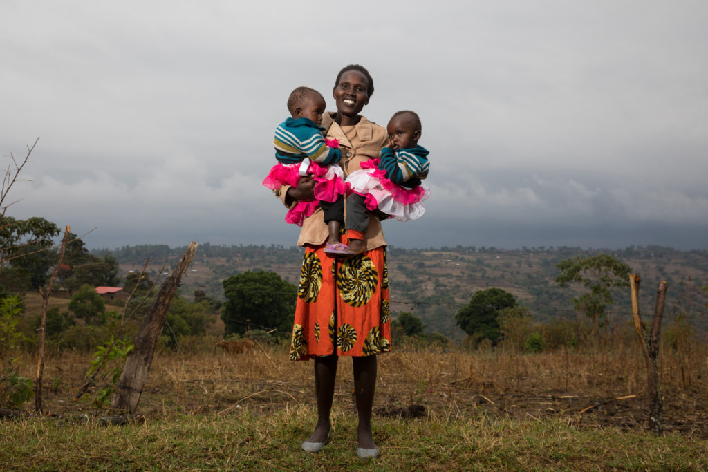 Woman stands and holds two babies