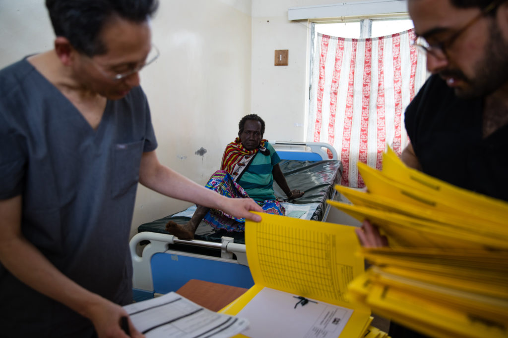 Medical staff look at documents with woman sitting on hospital bed in the background