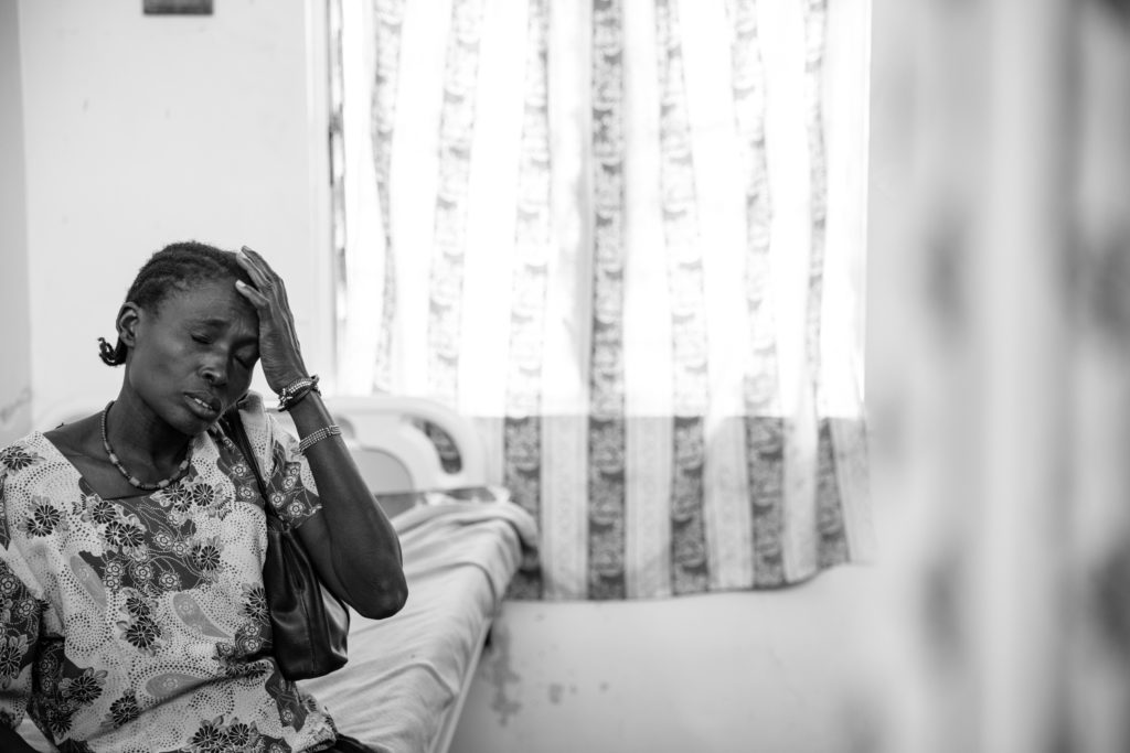 Woman sitting on hospital bed closes her eyes and has one hand on her head