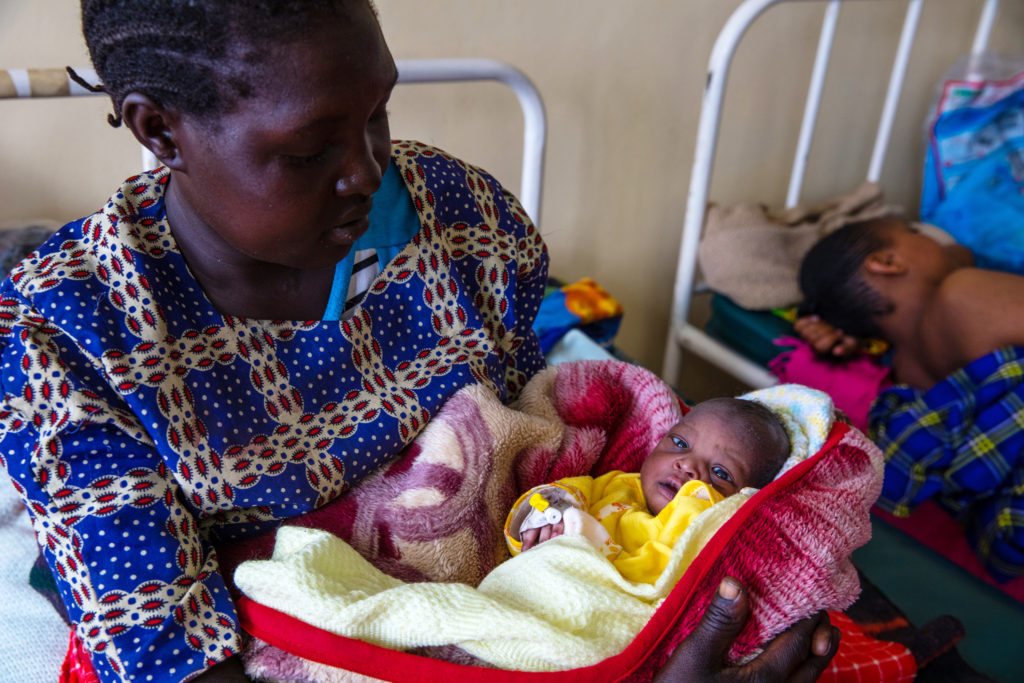 Woman on hospital bed holds baby in a blanket