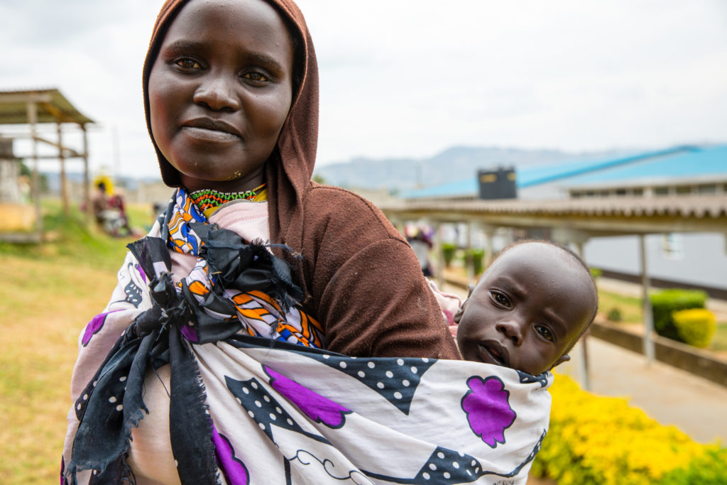 Woman carrying baby on her back smiles