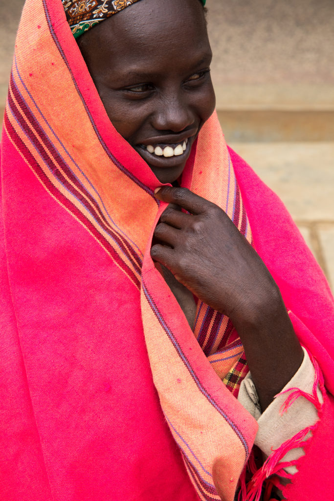 Woman wrapped in blanket smiles to the side