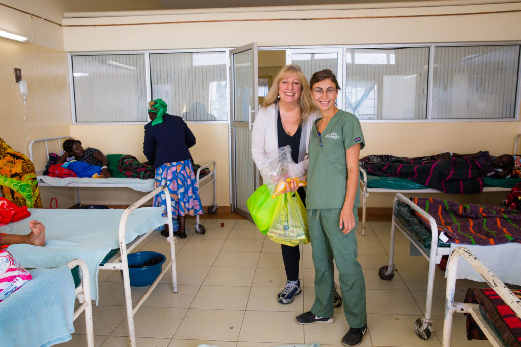 Medical staff stand and smile in a hospital room