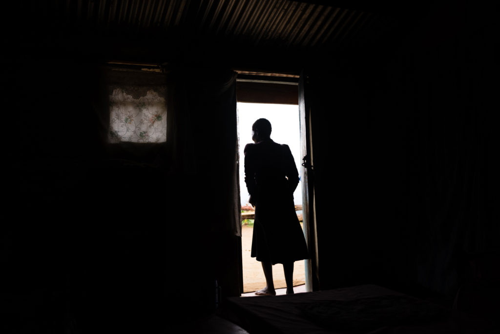 Woman inside room stands at door and looks outside