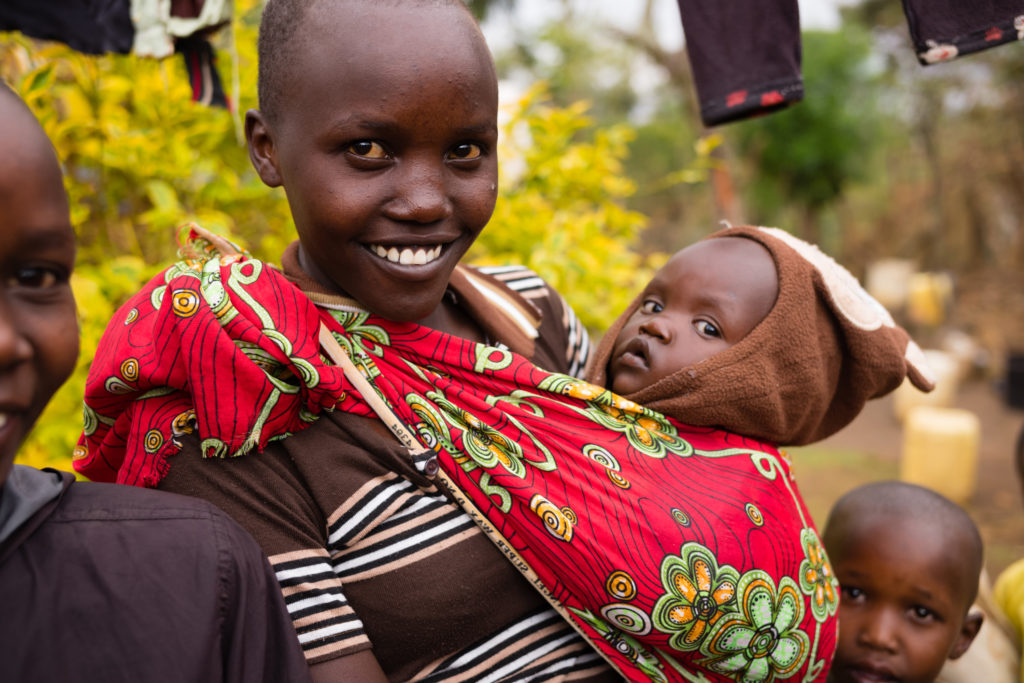 Woman carrying baby smiles