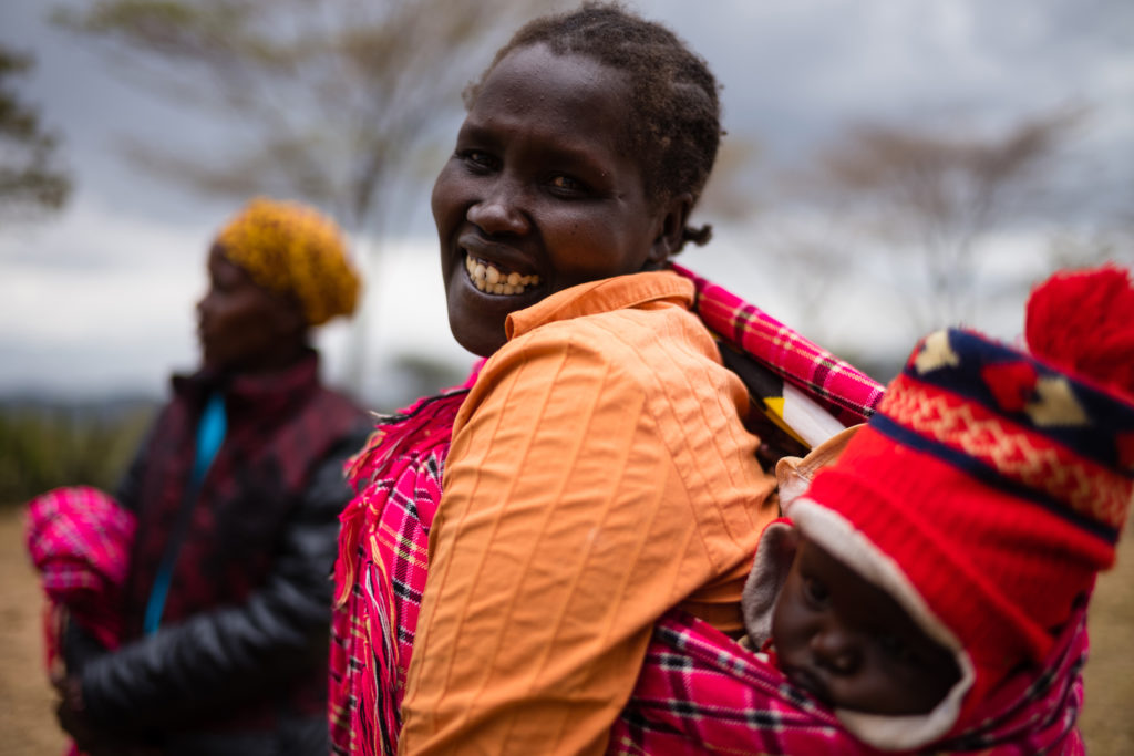 Woman carrying baby on back smiles