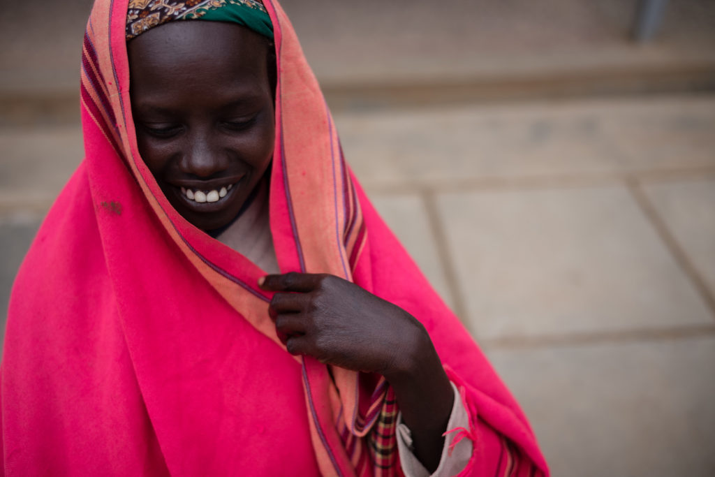 Women wrapped in fabric smiles and looks down