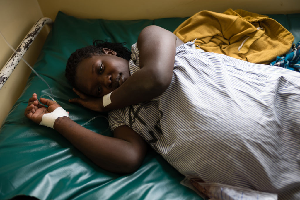 Pregnant woman lies on hospital bed receiving IV fluid