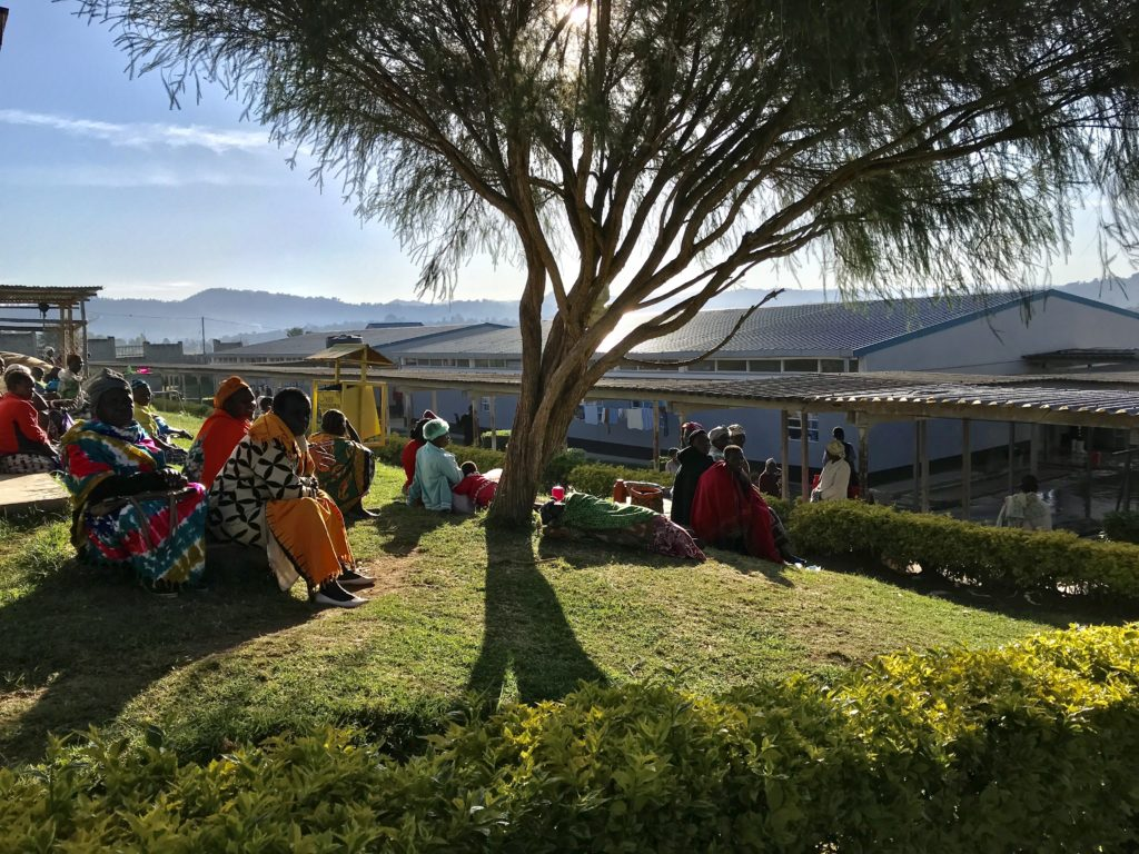 People sit on grass outside hospital