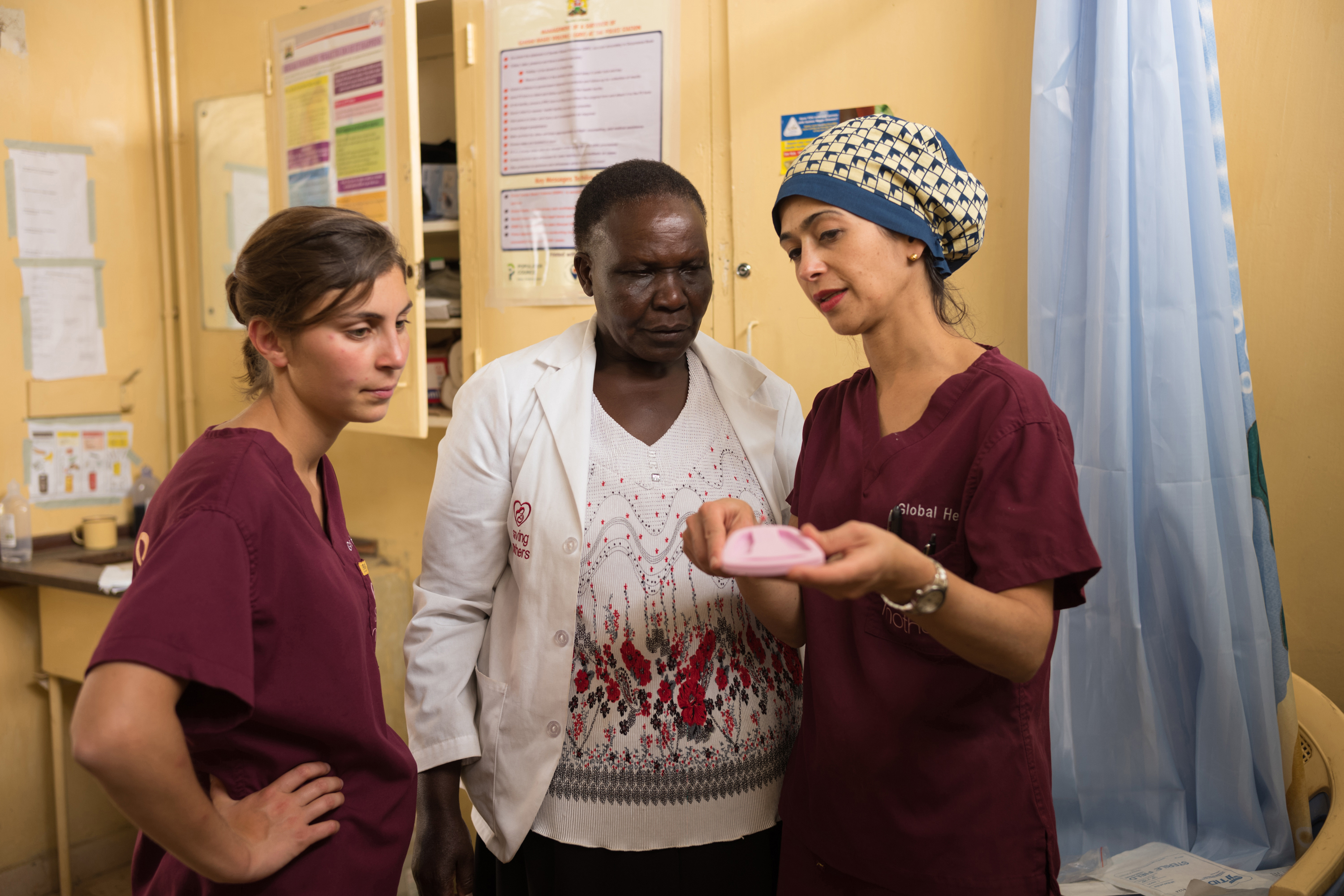 Saving Mothers fellow, Leah Jones, Antonet Kpar, and Dr. Tara Shirazian review the steps to insert an IUD on March 9, 2018 in Kapenguria, Kenya.    Saving Mothers visited West Pokot, Kenya and screened over 300 women and provided many types of surgery include molar pregnancy, ectopic pregnancy, hysterectomy, prolapse and fistula.